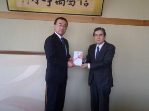 八子理事長(写真・右)から仲野教育長に贈呈