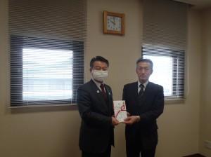 小野澤理事長(写真・左)から小出特別支援学校中田校長に贈呈