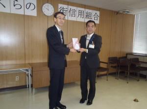 長谷川理事長(写真・左)から五泉市こども課の佐久間課長様に贈呈