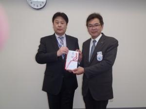 桐生常勤理事(写真・左)からJR東日本新潟支社の昆副課長様に贈呈