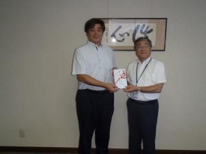 黒石理事長(写真・右)から清水代表に贈呈