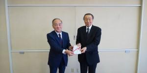 三浦常勤監事(写真・左)から本間会長に贈呈